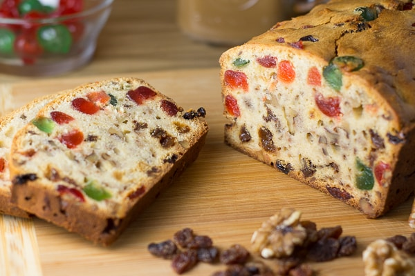 Fruitcake - a cross section of the fruitcake with glace cherries in the background and raisins, walnuts in the foreground