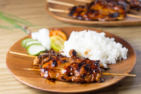 Filipino chicken barbecue skewered and served on a plate with rice and vegetables